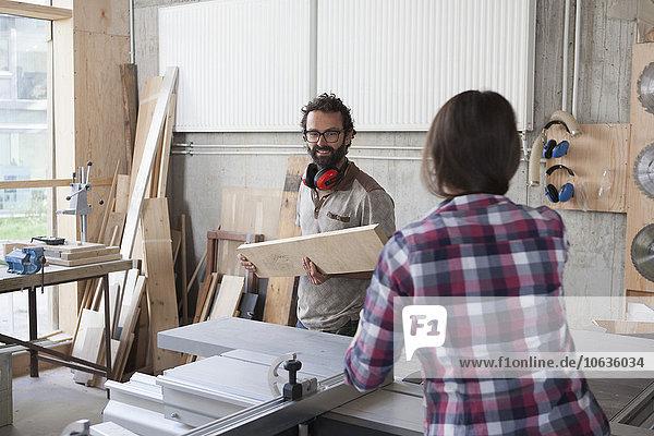 Schreinerinnen und Schreiner arbeiten in der Werkstatt zusammen.