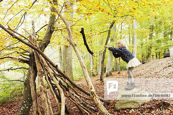 Girl throwing log in forest