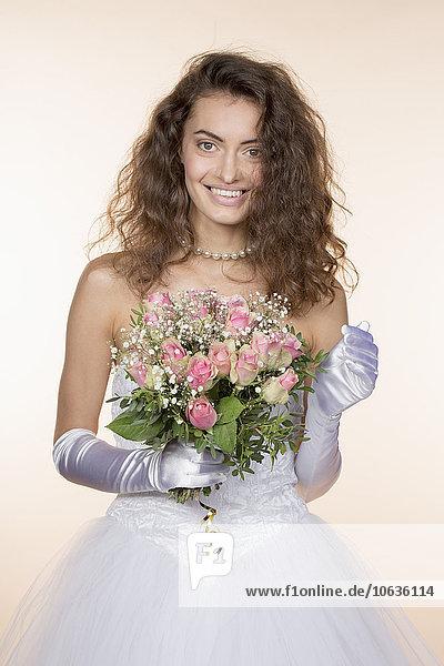 Porträt der glücklichen Braut mit Blumenstrauß vor farbigem Hintergrund