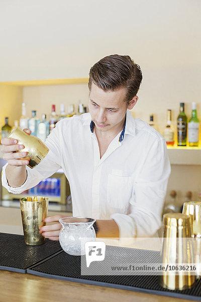 Bartender making drink at counter in Lebanese restaurant