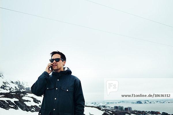 Handy benutzen Mann bedecken Himmel Feld Kurznachricht jung Schnee