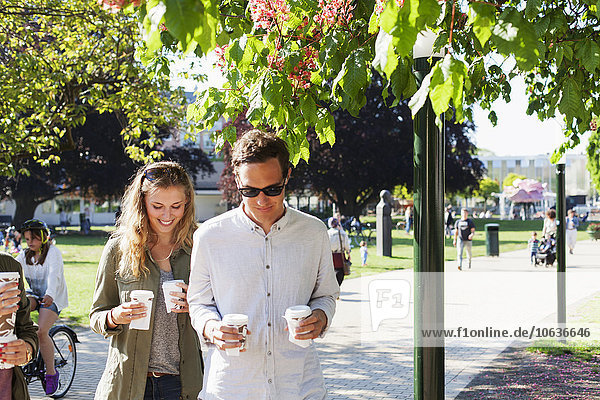 Couple holding disposable cups while walking on street at park