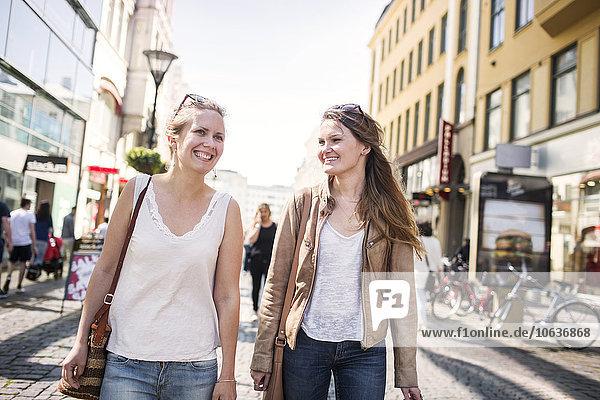 Happy shopaholic friends walking on cobblestone street
