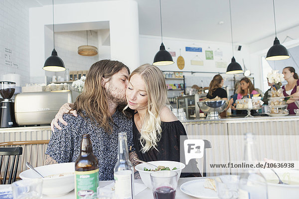 Young man kissing woman on cheek while sitting at restaurant table