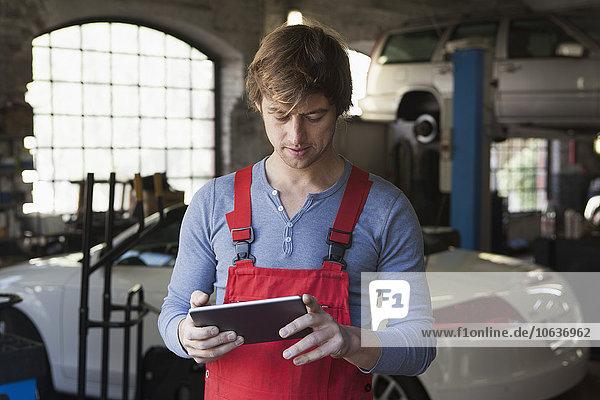 Mechanic using digital tablet at garage