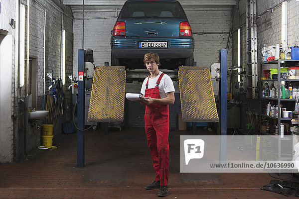 Portrait of confident mechanic holding clipboard at garage