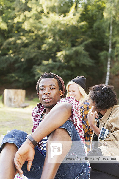 Portrait of man relaxing in forest with female friends in background