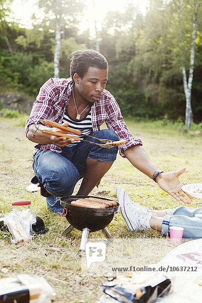 Mann geben Picknick Wurst Teller jung gegrillt