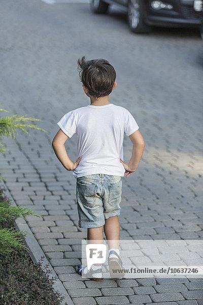 Rückansicht des Jungen mit den Händen auf der Hüfte stehend auf der Straße