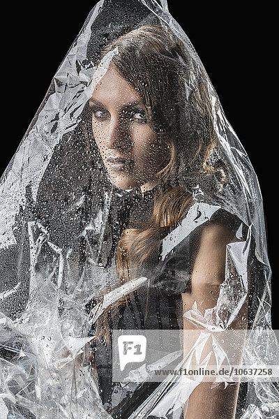 Portrait of woman wrapped in plastic against black background