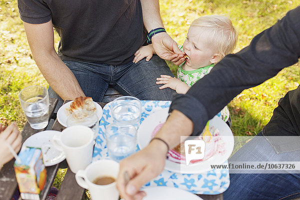 High angle view of father feeding baby boy at park