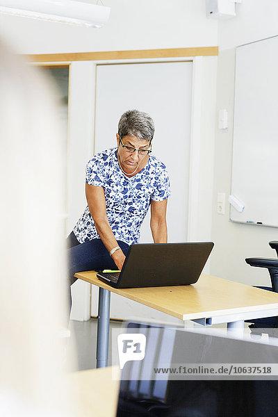 Female professor using laptop at desk in classroom