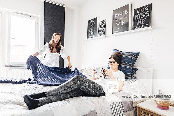 Interior zu Hause Frau Buch Produktion Bett Taschenbuch Freund vorlesen