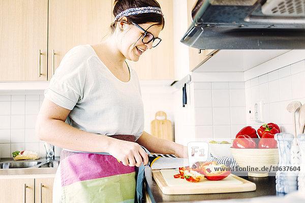 Frau lächeln schneiden Küche rot Peperoni Glocke Tresen