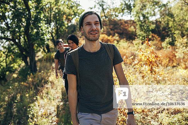 Lächelnder junger Mann beim Wandern mit Freunden im Wald