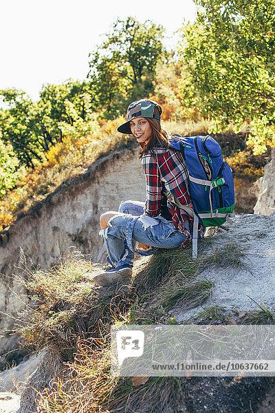 Porträt einer jungen Frau auf dem Berg sitzend