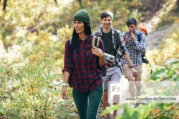 Junge Frau beim Wandern mit Freunden im Wald