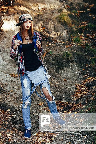 Ganzkörperporträt einer modischen jungen Frau in zerrissenen Jeans im Wald
