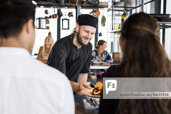 Fröhlichkeit Essgeschirr geben Restaurant Kunde Köchin