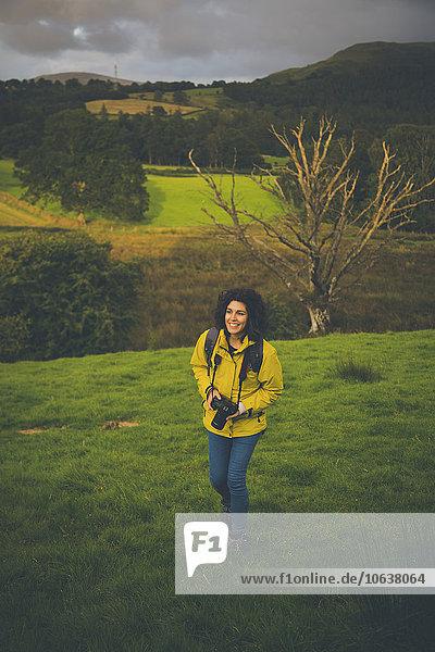 Hochwinkelaufnahme einer glücklichen Frau mit Kamera auf einem grasbewachsenen Hügel