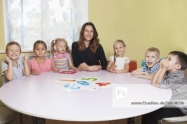 Porträt eines glücklichen Lehrers mit Kindern am Tisch im Klassenzimmer