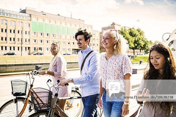 Fröhlichkeit Freundschaft gehen Straße jung Fahrrad Rad