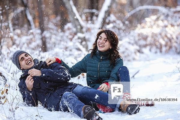 Verspieltes junges Paar in voller Länge auf verschneitem Feld sitzend