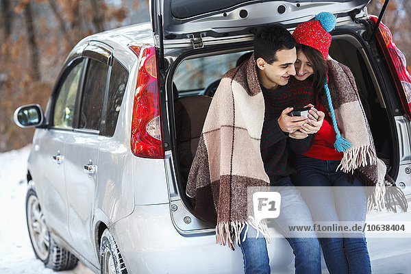 Happy young couple having coffee while sitting in boot of car during winter