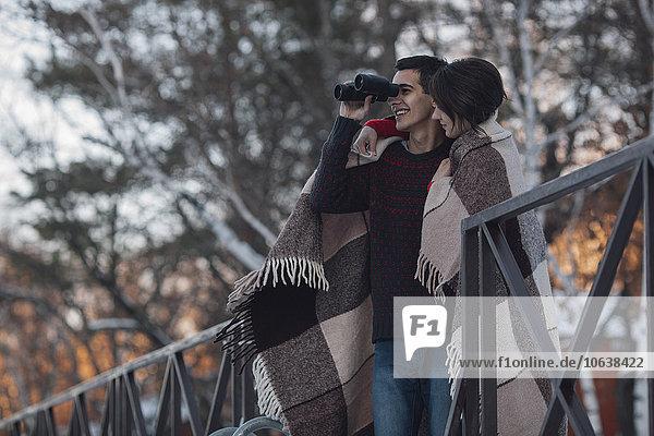 Junge Frau mit Mann im Winter durchs Fernglas schauend
