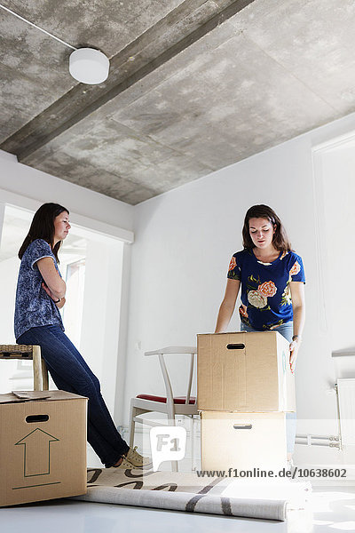 Woman looking at friend moving boxes