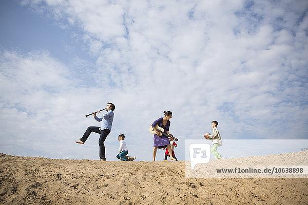 Flachwinkelansicht der Familie auf der Sanddüne gegen den bewölkten Himmel