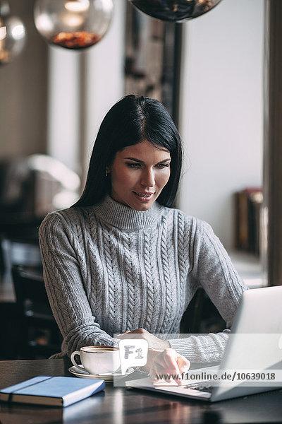 Junge Geschäftsfrau mit Laptop am Tisch im Café