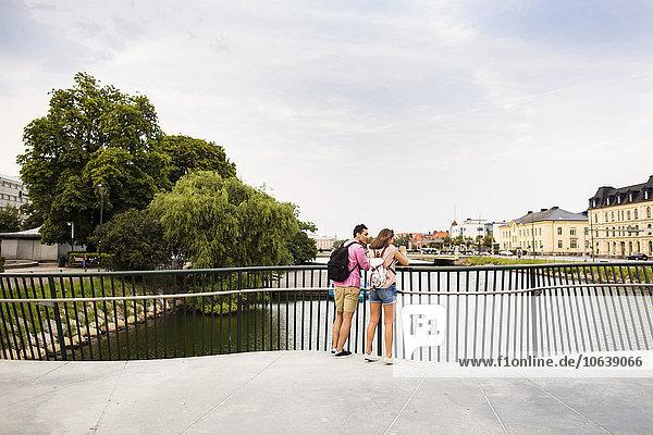 Fußgängerbrücke stehend Freundschaft über Großstadt Fluss Rückansicht Ansicht