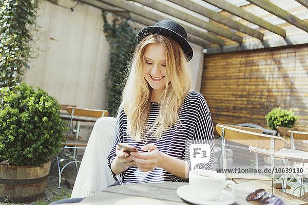 junge Frau junge Frauen lächeln Hut Cafe Kleidung Kaffee telefonieren