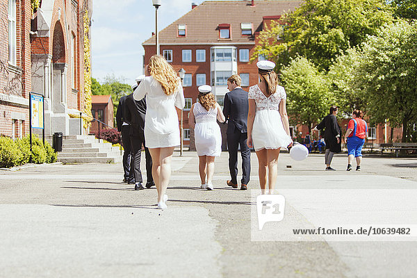 Rear view of male and female graduates walking on street