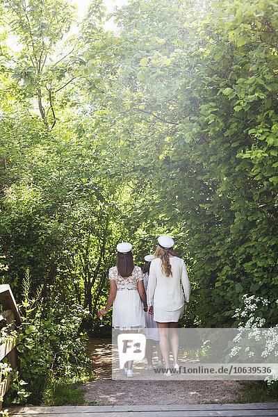 Rear view of female graduates walking at park