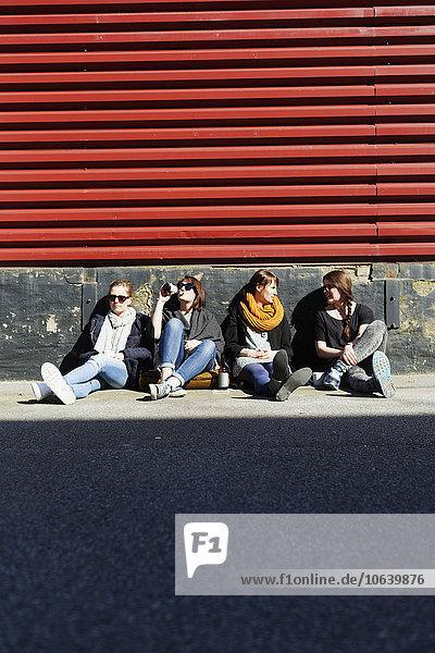 Friends sitting on street