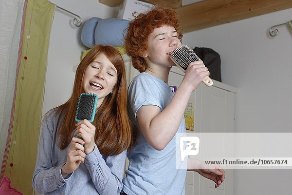 Children  boy and girl singing into hairbrush as microphone  Germany  Europe