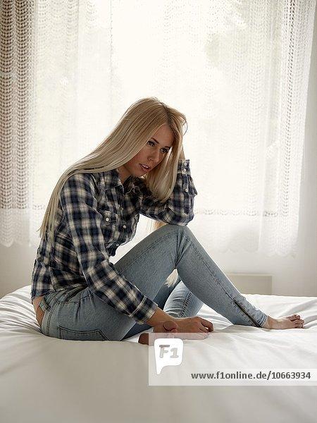junge Frau junge Frauen sitzend Bett Nachdenklichkeit
