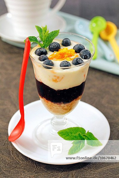 Cup with yogurt  orange and blueberries.