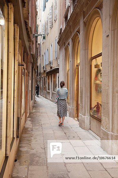 Young Woman Walking down Calle Frezzaria Street  Venice  Italy.