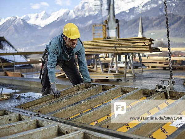 Bauarbeiter hebt mit einem Kran eine Schalungswand auf und bereitet eine Rahmenschalung vor  Innsbruck Land  Tirol  Österreich  Europa
