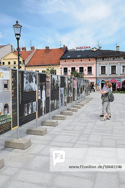 People viewing photographic exhibition recording life of Pope John Paul II in Town Square  Wadowice  Poland.