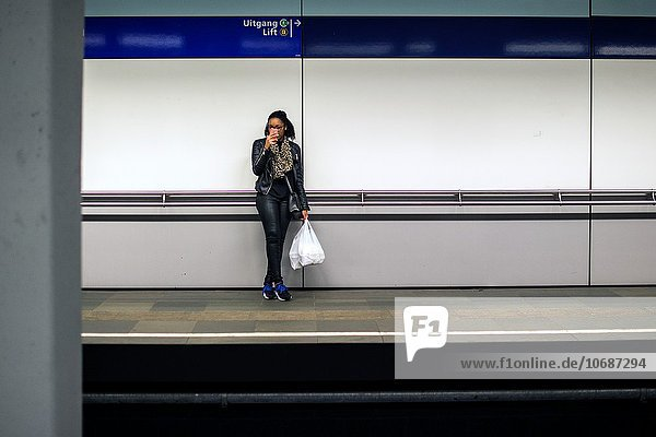 Rotterdam  Netherlands. Young African woman taking smartphone photo's while waiting for her connecting subway train.