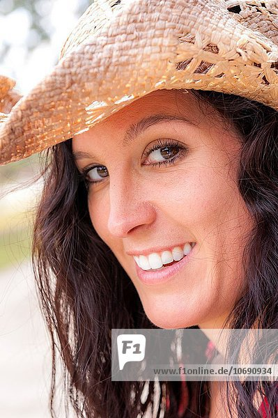 Portrait of a 38 year old brunette woman wearing a straw hat outdoors.