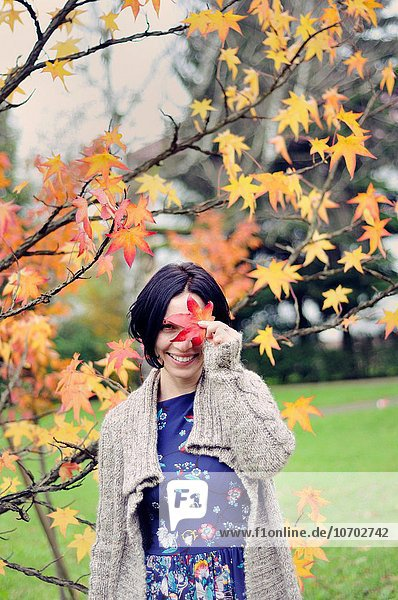 nahe Frau lächeln Pflanzenblatt Pflanzenblätter Blatt halten Herbst Mittelpunkt Erwachsener