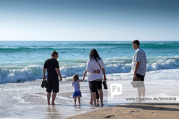 A family standing on the shoreline at Fistral beach in Newquay  Cornwall.