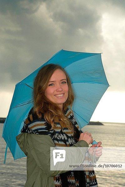 junge Frau junge Frauen Tag lächeln Regenschirm Schirm Meer Regen blau