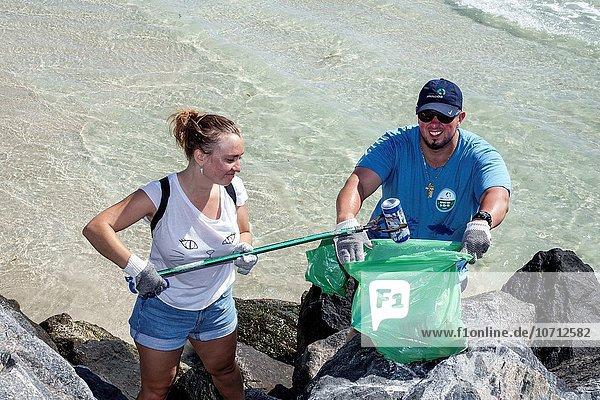 Jugendlicher Mann Hispanier verteilen Dose sauber aufräumen Mädchen Florida Miami Beach Freiwilliger