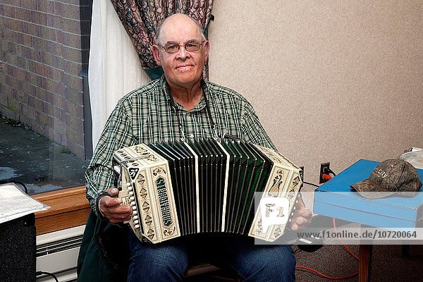 Senior volunteer musician playing the accordion. Good Samaritan Society Nursing Home. Battle Lake Minnesota MN USA.